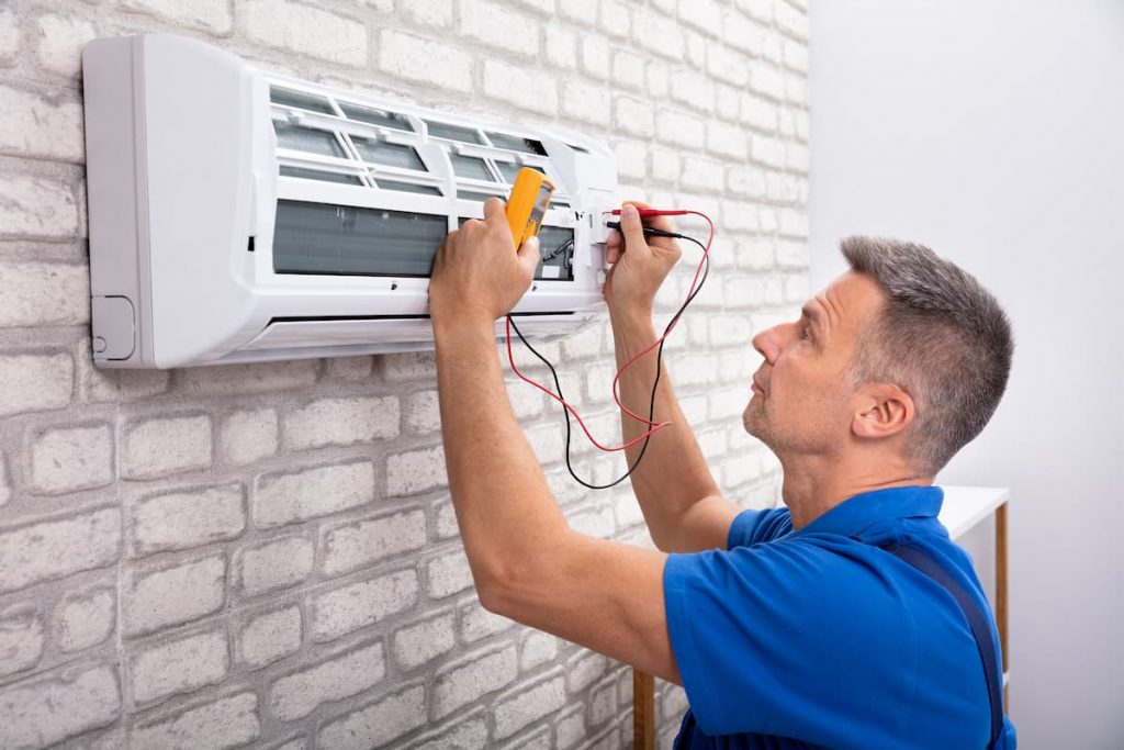 Male Electrician Checking a Commercial Air Conditioner With Digital Multimeter